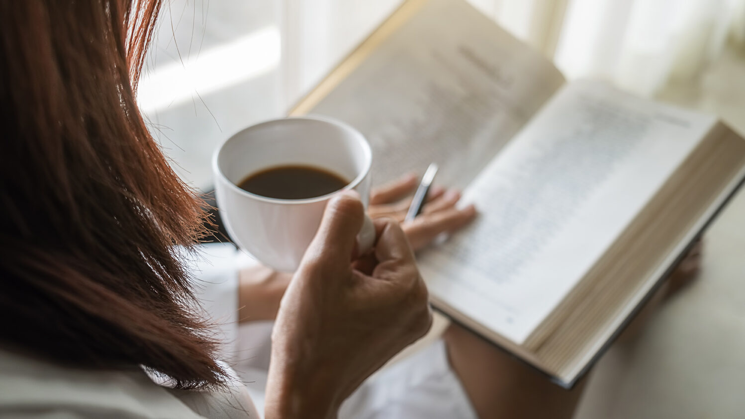 Asian woman holding cup of coffee and reading a book beside the window after get up in morning. Morning lifestyle concept.
